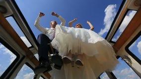 Χορεύοντας και κυματίζοντας χέρια ευτυχών νέων εύθυμων γαμήλιων ζευγών και πόδια στην αναδρομική κορυφή λεωφορείων στον τομέα Όψη απόθεμα βίντεο