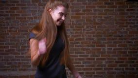 Χορεύοντας και πηδώντας πυροβολισμός του κοκκινομάλλους θηλυκού στο stdio τούβλου, που είναι στην καλές διάθεση και τη μορφή, συν απόθεμα βίντεο