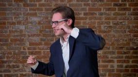 Χορεύοντας καυκάσιος επιχειρηματίας που κινείται ευτυχώς και απρόσεκτος, υπόβαθρο τούβλου, εταιρική εμφάνιση απόθεμα βίντεο