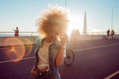 Χορεύοντας μοντέρνο κορίτσι σε έναν περίπατο πόλεων Όμορφη και εύθυμη νέα γυναίκα με την πολύβλαστη τρίχα, υπαίθρια Στοκ εικόνα με δικαίωμα ελεύθερης χρήσης