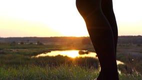Χορεύοντας πόδια της λεπτής γυναίκας στο ηλιοβασίλεμα σε σε αργή κίνηση φιλμ μικρού μήκους