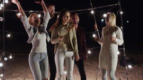 Χορεύοντας φίλοι με τα οβελίδια στα χέρια τους που έχουν τη διασκέδαση στην παραλία βραδιού στο υπόβαθρο ενός ντεκόρ με τους λαμπ απόθεμα βίντεο