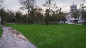 Χορτοτάπητας ποτίσματος ψεκαστήρων άρδευσης κήπων στο πάρκο κοντά στη διάβαση πεζών Αυτοματοποιημένο περιστρεφόμενο σύστημα άρδευ φιλμ μικρού μήκους