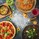Χορτοφάγα τρόφιμα - πίτσα με τα λαχανικά, τα ποτά σαλάτας, πιτών και φρούτων στο σκοτεινό υπόβαθρο Επίπεδος βάλτε, τοπ άποψη τρόφ Στοκ Εικόνες