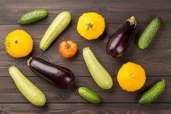 Χορτοφάγα υγιή τρόφιμα με τα λαχανικά Ντομάτα, αγγούρια, κολοκύθες θάμνων, κολοκύθια ND μελιτζανών στο σκοτεινό ξύλινο πίνακα Στοκ Εικόνες