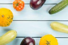 Χορτοφάγα υγιή τρόφιμα με τα λαχανικά Ντομάτα, αγγούρια, κολοκύθες θάμνων, eggplantsand κολοκύθια στον μπλε ξύλινο πίνακα με τη S Στοκ Εικόνα