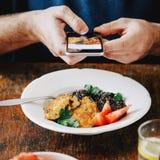 Χορτοφάγος ατόμων που παίρνει τα τρόφιμα εικόνων που τρώει στο smartphone Στοκ φωτογραφία με δικαίωμα ελεύθερης χρήσης