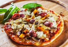 Χορτοφάγος πίτσα με το τυρί μοτσαρελών, τις ελιές, τα μανιτάρια, το πιπέρι και το φρέσκο βασιλικό Ιταλική πίτσα στον ξύλινο πίνακ στοκ εικόνα