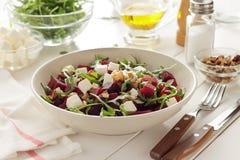 Χορτοφάγος σαλάτα με τα παντζάρια, το arugula, τα ξύλα καρυδιάς και το τυρί στο κεραμικό πιάτο στον άσπρο πίνακα κουζινών Στοκ Εικόνες