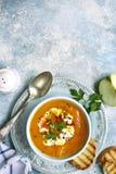 Χορτοφάγος σούπα καρότων κολοκύθας με το μήλο και πιπερόριζα σε ένα vintag στοκ εικόνα