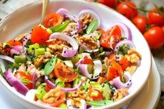 Χορτοφάγου, ακατέργαστης σαλάτα Detox, με την ντομάτα, κρεμμύδια και ξύλα καρυδιάς Στοκ Φωτογραφία