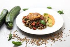 Χορτοφάγο μαγείρεμα Ζωηρόχρωμο φυτικό meatless πιάτο Βρασμένες φακές με τον πουρέ καρότων και τα ψημένα στη σχάρα κολοκύθια στοκ φωτογραφία με δικαίωμα ελεύθερης χρήσης