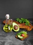 Χορτοφάγο σάντουιτς αβοκάντο Αβοκάντο, φύλλα σαλάτας και οργανική σάλτσα σε ένα μαύρο υπόβαθρο Γαλλική κουζίνα διάστημα αντιγράφω Στοκ Εικόνες