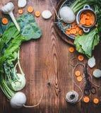 Χορτοφάγο υπόβαθρο τροφίμων με τα φρέσκα οργανικά τοπικά λαχανικά στον ξύλινο αγροτικό πίνακα κουζινών, τοπ άποψη, μαγειρεύοντας  Στοκ Εικόνες
