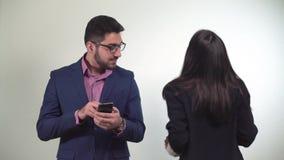 Χορός εργαζομένων γραφείων brunette κοριτσιών ξένοιαστος δίπλα σε έναν συνάδελφο ενώ εξετάζει το smartphone του απόθεμα βίντεο