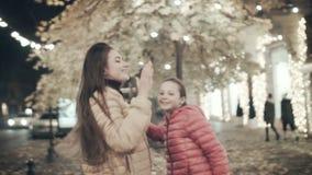 Χορός κορών Mom και εφήβων το βράδυ φθινοπώρου κατά μήκος της οδού Δύο νέα κορίτσια ακούνε τη μουσική στα ακουστικά μέσα φιλμ μικρού μήκους