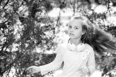 Χορός παιδιών στη μουσική στο θερινό πάρκο Το μικρό κορίτσι απολαμβάνει τη μουσική στα ακουστικά υπαίθρια Χορευτής παιδιών με τη  Στοκ Φωτογραφίες