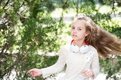 Χορός παιδιών στη μουσική στο θερινό πάρκο Το μικρό κορίτσι απολαμβάνει τη μουσική στα ακουστικά υπαίθρια Χορευτής παιδιών με τη  Στοκ φωτογραφία με δικαίωμα ελεύθερης χρήσης