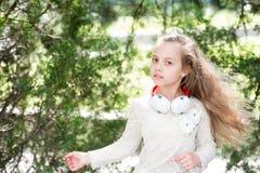 Χορός παιδιών στη μουσική στο θερινό πάρκο Το μικρό παιδί απολαμβάνει τη μουσική στα ακουστικά υπαίθρια Χορευτής κοριτσιών με τη  Στοκ Εικόνες