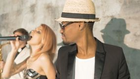 Χορός τεσσάρων ο επαγγελματικός μουσικών και τραγουδά Όμορφη νέα ξανθή γυναίκα και αφρικανικό τραγούδι ανδρών Ο λευκός μουσικός φιλμ μικρού μήκους