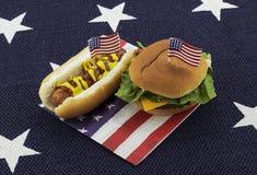 Χοτ-ντογκ και χάμπουργκερ σε μια πετσέτα και μια οδοντογλυφίδα αμερικανικών σημαιών στοκ φωτογραφία με δικαίωμα ελεύθερης χρήσης
