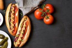Χοτ-ντογκ με την ντομάτα, μαριναρισμένα αγγούρια, κρεμμύδι Στοκ φωτογραφίες με δικαίωμα ελεύθερης χρήσης