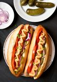Χοτ-ντογκ με την ντομάτα, μαριναρισμένα αγγούρια, κρεμμύδι Στοκ Εικόνες