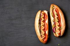 Χοτ-ντογκ με την ντομάτα, μαριναρισμένα αγγούρια, κρεμμύδι Στοκ Εικόνα