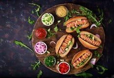 Χοτ-ντογκ με το αγγούρι, την ντομάτα και το κόκκινο κρεμμύδι στο ξύλινο υπόβαθρο Στοκ Φωτογραφία