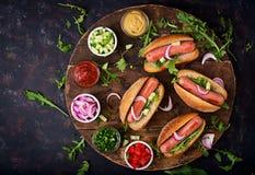 Χοτ-ντογκ με το αγγούρι, την ντομάτα και το κόκκινο κρεμμύδι στο ξύλινο υπόβαθρο Στοκ εικόνα με δικαίωμα ελεύθερης χρήσης