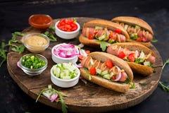 Χοτ-ντογκ με το αγγούρι, την ντομάτα και το κόκκινο κρεμμύδι Στοκ φωτογραφία με δικαίωμα ελεύθερης χρήσης