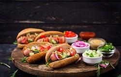 Χοτ-ντογκ με το αγγούρι, την ντομάτα και το κόκκινο κρεμμύδι Στοκ Εικόνες