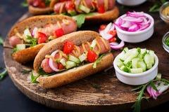 Χοτ-ντογκ με το αγγούρι, την ντομάτα και το κόκκινο κρεμμύδι Στοκ Εικόνα