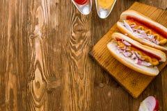 Χοτ-ντογκ με το κέτσαπ και τη μουστάρδα και τα κόκκινα κρεμμύδια Στοκ φωτογραφία με δικαίωμα ελεύθερης χρήσης