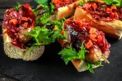 Χοτ-ντογκ λουκάνικων του Cumberland με το καραμελοποιημένο κρεμμύδι, ψημένα κόκκινα πιπέρια Στοκ φωτογραφία με δικαίωμα ελεύθερης χρήσης