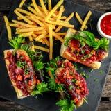 Χοτ-ντογκ λουκάνικων του Cumberland με το καραμελοποιημένο κρεμμύδι, ψημένα κόκκινα πιπέρια, τηγανιτές πατάτες Στοκ φωτογραφία με δικαίωμα ελεύθερης χρήσης