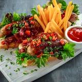 Χοτ-ντογκ λουκάνικων του Cumberland με το καραμελοποιημένο κρεμμύδι, ψημένα κόκκινα πιπέρια, τηγανιτές πατάτες Στοκ Φωτογραφίες