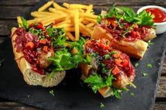 Χοτ-ντογκ λουκάνικων του Cumberland με το καραμελοποιημένο κρεμμύδι, ψημένα κόκκινα πιπέρια, τηγανιτές πατάτες Στοκ Εικόνες