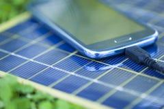 Χρέωση του κινητού τηλεφώνου με τον ηλιακό φορτιστή Στοκ Φωτογραφία