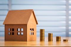 Χρήματα αποταμίευσης για να αγοράσει ένα νέο σπίτι των χρημάτων του στη piggy τράπεζα Χαμηλότερο κόστος και φόρος στοκ φωτογραφίες