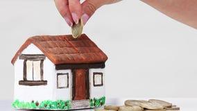 Χρήματα αποταμίευσης γυναικών σε ένα κιβώτιο χρημάτων σπιτιών απόθεμα βίντεο