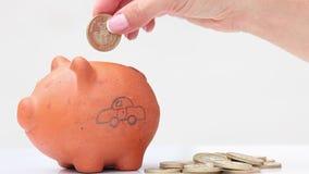 Χρήματα αποταμίευσης γυναικών σε μια παραδοσιακή piggy τράπεζα αργίλου για ένα αυτοκίνητο απόθεμα βίντεο