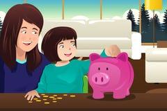 Χρήματα αποταμίευσης κορών μητέρων σε ένα piggybank ελεύθερη απεικόνιση δικαιώματος