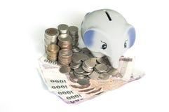 Χρήματα αποταμίευσης με την τράπεζα Piggy Στοκ φωτογραφία με δικαίωμα ελεύθερης χρήσης