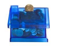 Χρήματα αποταμίευσης στην μπλε τράπεζα σπιτιών Στοκ φωτογραφία με δικαίωμα ελεύθερης χρήσης