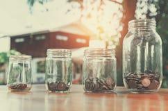 χρήματα αποταμίευσης στο γυαλί βάζων και το υπόβαθρο σπιτιών, χρηματοδότηση έννοιας Στοκ φωτογραφίες με δικαίωμα ελεύθερης χρήσης