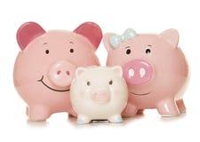 Χρήματα αποταμίευσης ως piggy τράπεζες οικογενειών Στοκ εικόνα με δικαίωμα ελεύθερης χρήσης