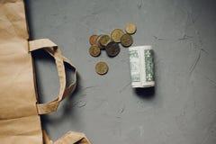 Χρήματα δολαρίων μετρητών, ευρο- νομίσματα με μια συσκευασία της Kraft σε γκρίζο στοκ εικόνα