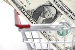 Χρήματα δολαρίων με το κάρρο αγορών στο άσπρο υπόβαθρο που πυροβολείται στο στήριγμα στοκ φωτογραφία