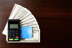 Χρήματα δολαρίων, συσκευή πληρωμής και τραπεζική κάρτα στο ξύλινο υπόβαθρο στοκ εικόνες